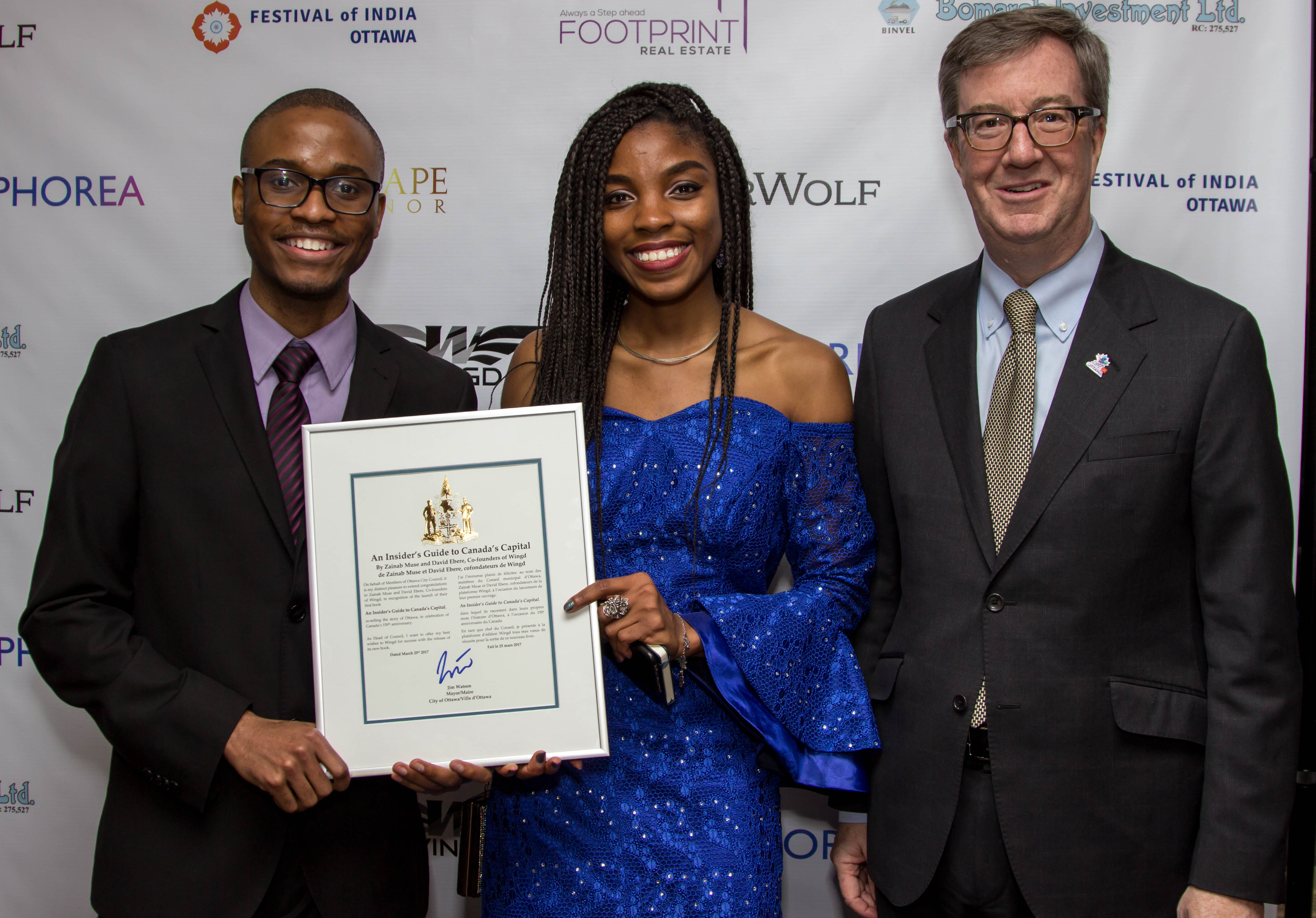 Mayor Jim Watson awarding the founders of Wingd, Zainab Muse and David Ebere with a plaque commemorating their efforts